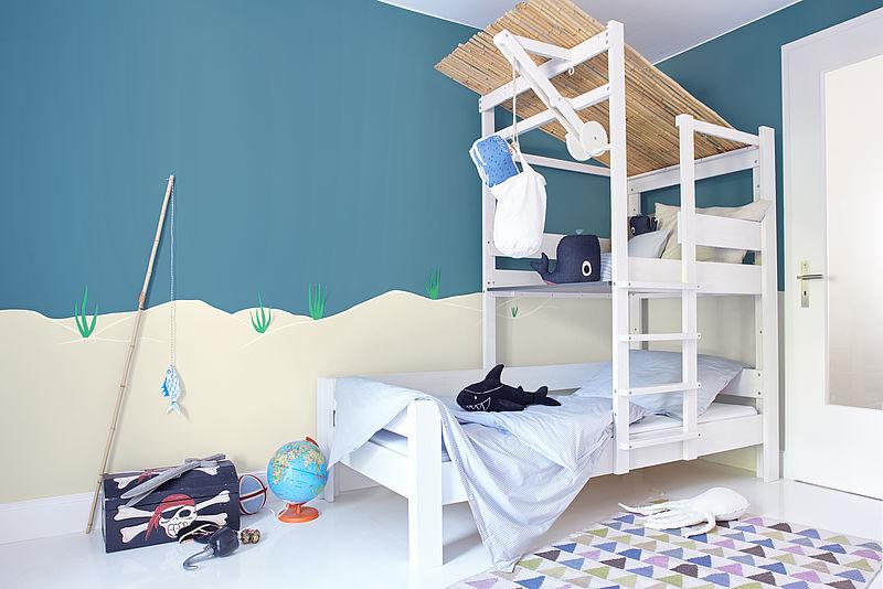 Modernes Jungen Kinderzimmer in weiß und blau mit Fisch und Piraten Thema mit Alpina Farbenfreunde Farbe Seebärblau.