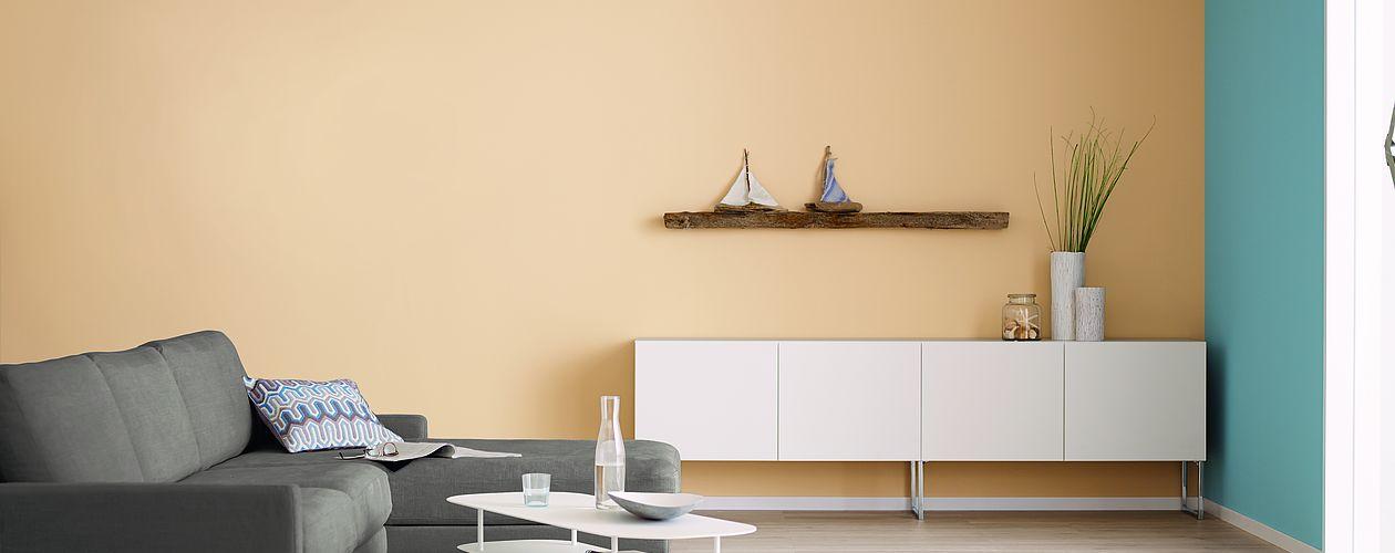 Wohnzimmer mit weißen und braunen Möbeln mit orange beiger Wand und blauen Akzenten.
