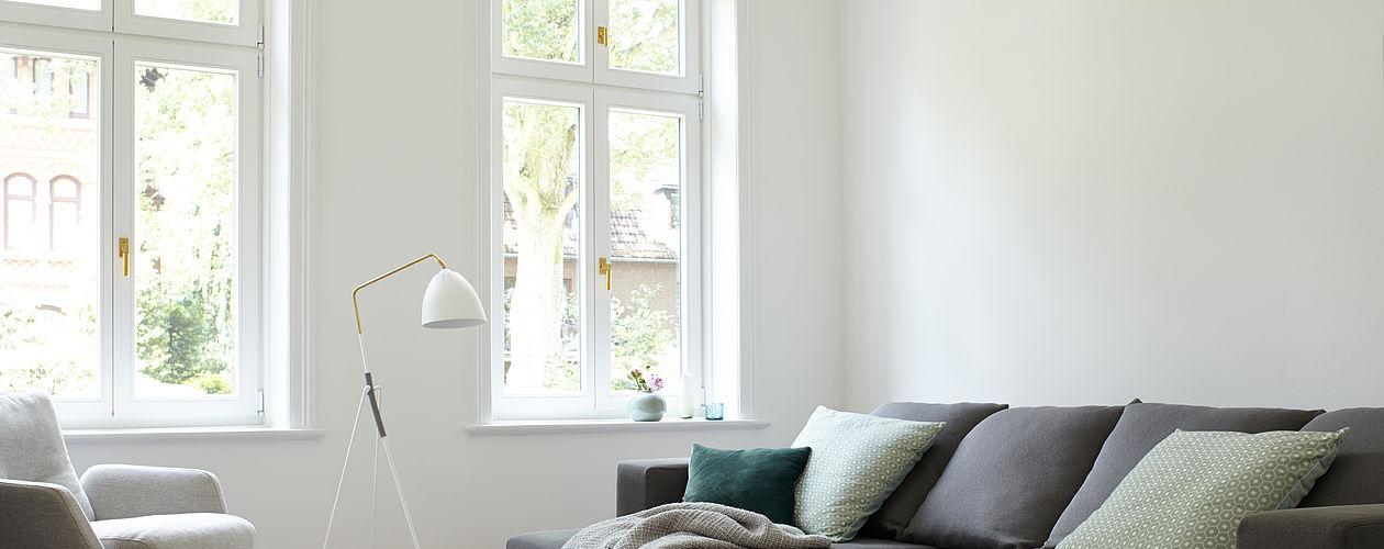 Helles, modernes Wohnimer mit grau-braunem Sofa vor einer weißen Wand.