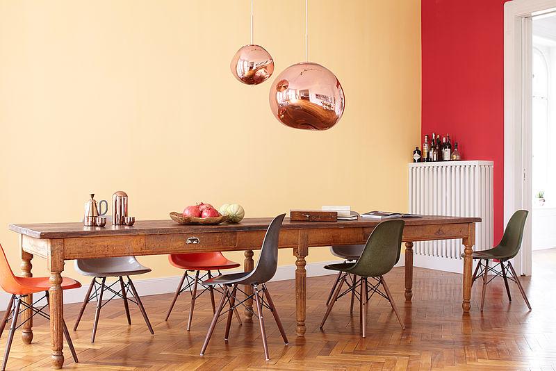 Warmes, gemütliches Esszimmer mit Holztisch und Messinglampen vor einer orange roten Wand in der Alpina Farbe Granatapfel und Sweet Home.