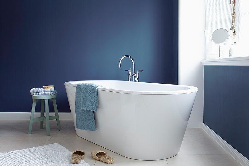 Weißes, modernes Badezimmer mit freistehender Badewanne und dunkel blauer Wand in der Alpina Farbe Blaue Stunde.